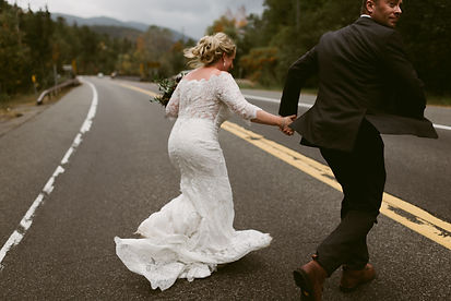 Bride and groom hold hands as they run across the road during their wedding in Lake Placid