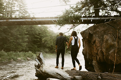 Couple holds hands as they explore a log during their engagement session in Wells, NY
