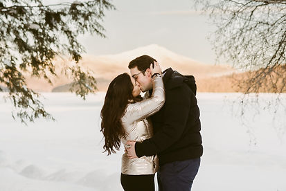 Couple kisses in front of Whiteface Mountain at sunset
