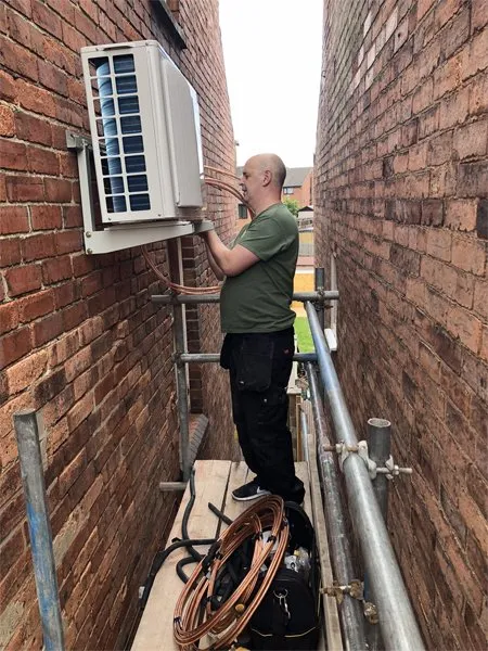 working on air conditioning unit on a platform.webp