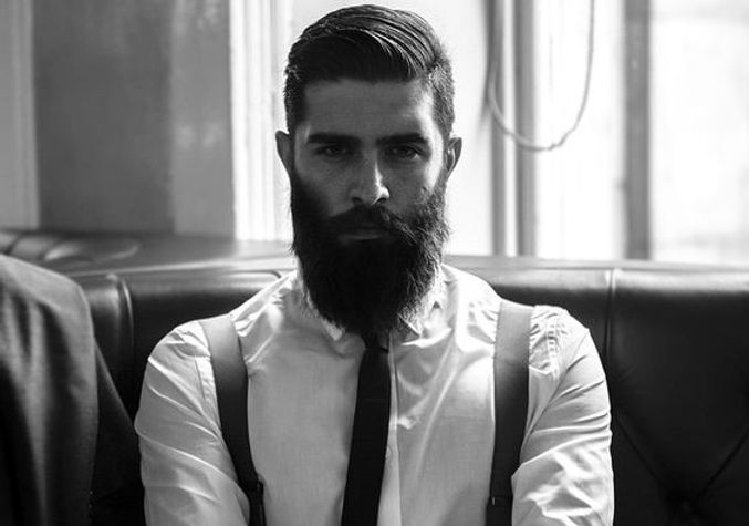 A bearded man who is looking very serioius about keeping his promise