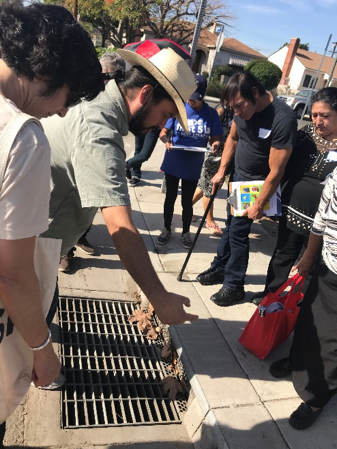 """Community leaders observing the """"water catch basin"""" which diverts thousands of cubic feet of storm water into an underground reservoir."""