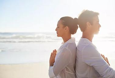 Couple méditant sur la plage.webp