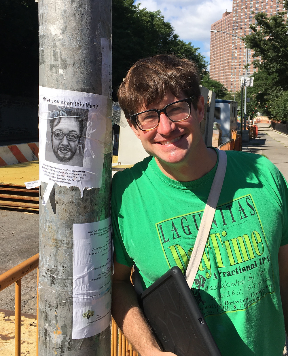"Artist Tom Sanford in front of a flyer for his show ""Have You Seen This Man/"""
