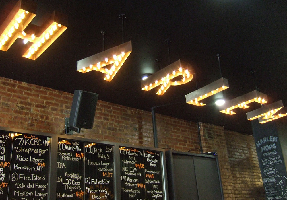 """A """"Harlem"""" bulb sign hangs from the ceiling at Harlem Hops"""