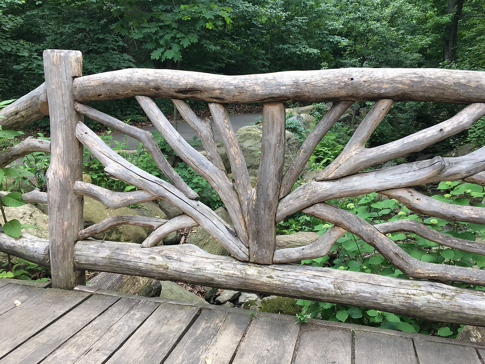 A rustic bridge creates a walkway over the stream in Central Park's Ravine