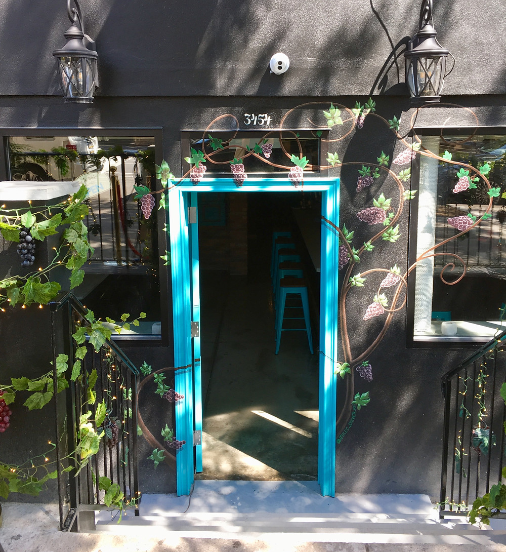 Harlem Wine Room has an inviting, wine-themed mural around its front door