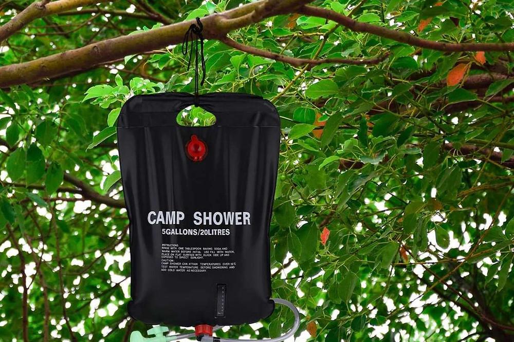 douche de camping accroché a l'arbre