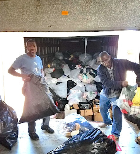 William ( on the left ) picking up the recycle clothing at the Free General Store Distribution Center