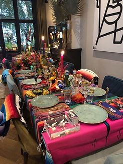 Dinning table in amsterdam with a colorfull table cloth, also candles, green ceramic plates and flowers.