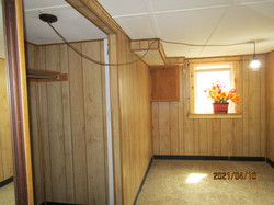 Basement bedroom has light wood-styled paneling, brown carpet, with escape window in case of fire.
