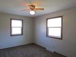 Deck-side bedroom has ceiling fan, carpet, 1 closet.