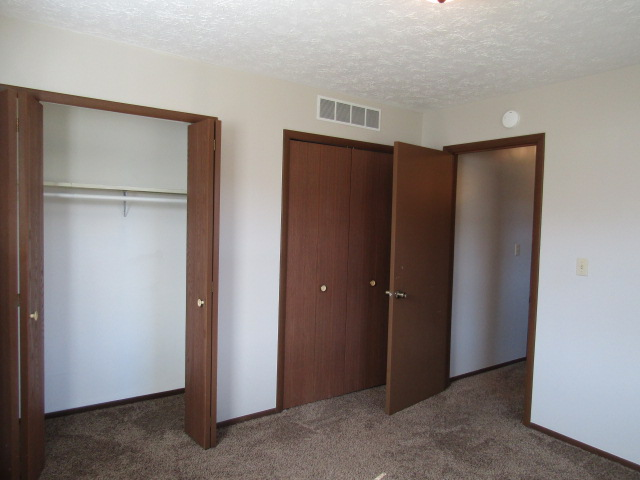 This bedroom has two large closets, carpeted.