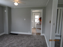 Living room is gray with white trim and new gray carpet.  Entry into kitchen.  Smoke alarm visible.