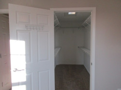 Interior view of walk-in closet with taupe colored carpet and wire shelf organizer.