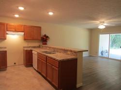 Kitchen, breakfast bar, living room, patio doors to covered deck.