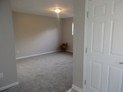 Lower level recreational room with taupe colored carpet and gray walls.