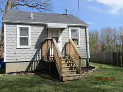 House rear porch is natural wood with small deck.