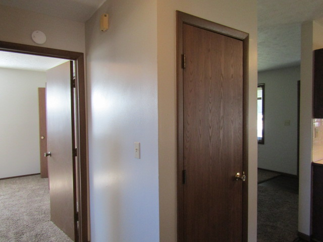 Hall view from deck side bedroom of living room and other bedroom.