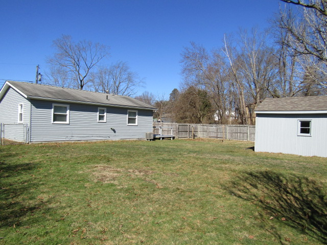 Fenced in portion of backyard, shed in photo.
