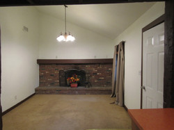 Living room has working wood fireplace.