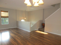 Living room has brown laminate flooring with upscale gray walls.