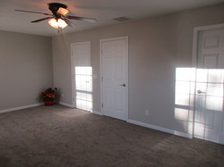 Primary bedroom is large with taupe colored carpet and gray walls.