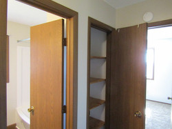 Hall view of linen closet and other bedroom.