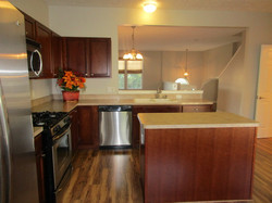 Kitchen has stainless steel appliances, cherry cabinets, beige countertops, island, and closet pantr