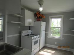 Kitchen has refrigerator & gas stove; gray with white trim; beige linoleum.