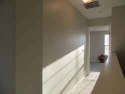 Hall to primary bedroom with taupe colored carpeting and gray walls.