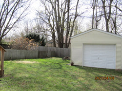 1-car garage has mandoor; easy lift overhead door. Yellow siding with white doors.