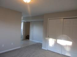 Rec room view of utility closet, vinyl flooring outside of garage door.