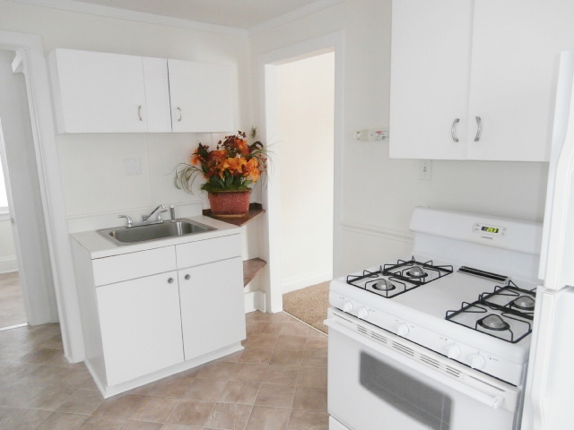 Kitchen has stove and refrigerator.