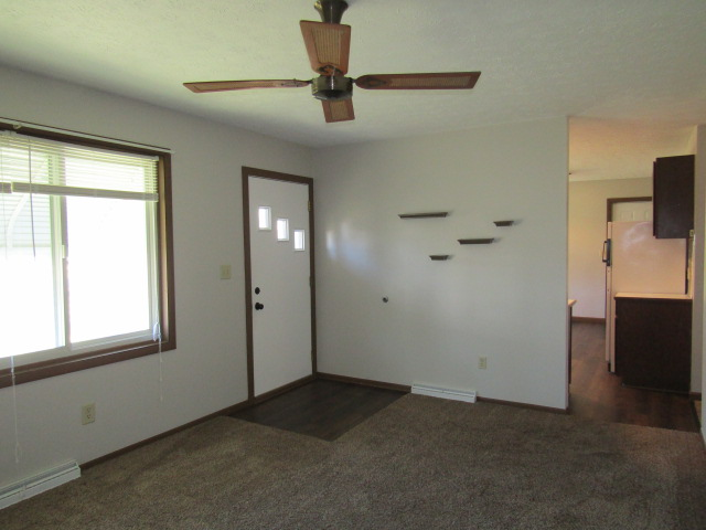 Front room has ceiling fan and carpeting.