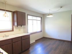 View of dinette.  Kitchen & dinette have brown laminate flooring.
