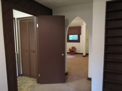 Same hall with view of bath entry, hot water tank cubby, bedroom.