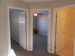 Steps to 2nd floor and upstairs hall are carpeted with gray paint.
