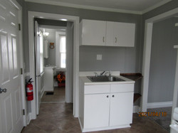 Kitchen view of sink & rear door, hall to bath and basement.  View of fire extinguisher.
