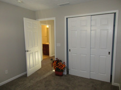 Middle bedroom has a central light, taupe colored carpet and gray paint.