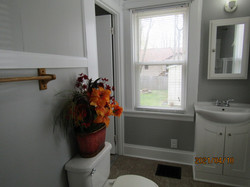 Bathroom is nice sized, 2 windows, gray paint with white trim; beige linoleum.