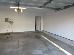 Two-car garage has finished white walls and cement floor.  Remote opener.