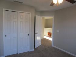 End bedroom has taupe carpet, gray paint, ceiling fan, & double door closet.
