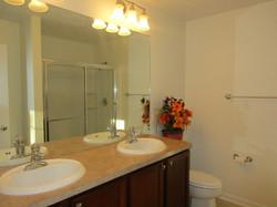 Bathroom has double sinks, large shower, towel racks, cherry sink cabinet, light colored vinyl floor