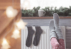 Woman warming up with feet on heater Win