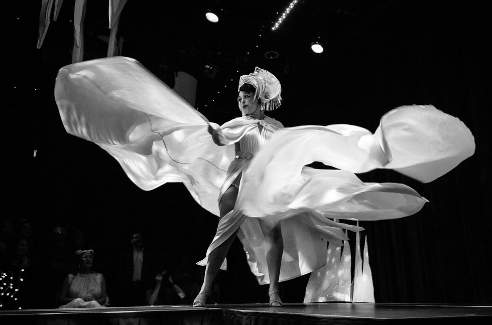 Black and white image of burlesque performer Nona Narcisse twirling in white fabric
