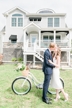 bright and airy wedding couple kissing with bicycle