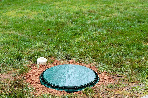 A riser lid at grade on top of a septic tank