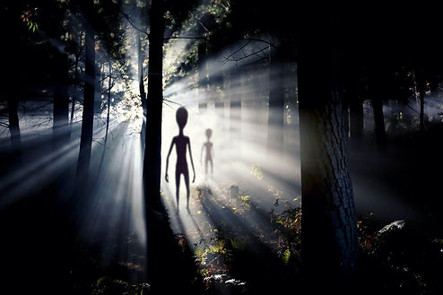 The meeting with an alien civilization - blurred aliens figure and light of an UFO spacesh