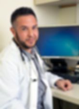 A transmasculine doctor in front of his